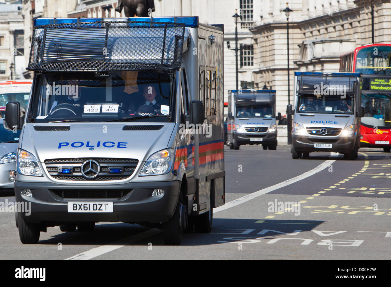 Three police riot vans, with sirens blaring, drive up a central London road, UK. - Stock Image