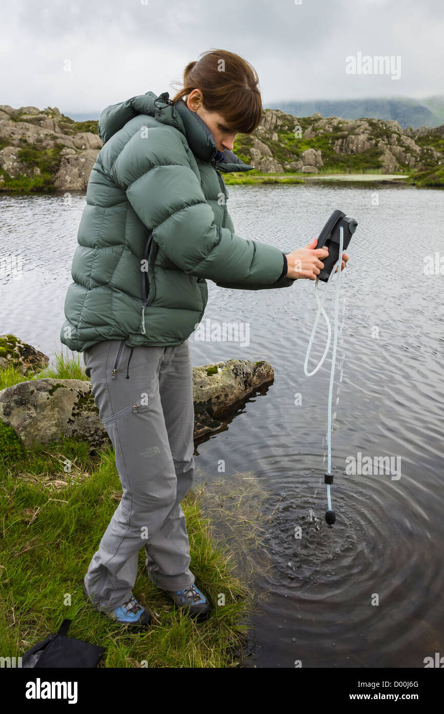 A woman filtering some water into a plastic bottle from a mountain tarn in the Lake District. - Stock Image