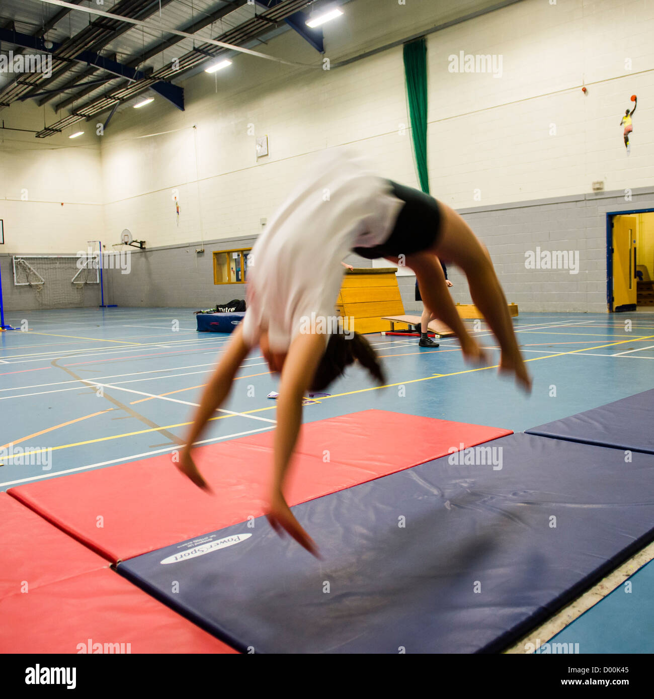 A girl in a Physical education class in the gymnasium at a secondary comprehensive school, Wales UK Stock Photo