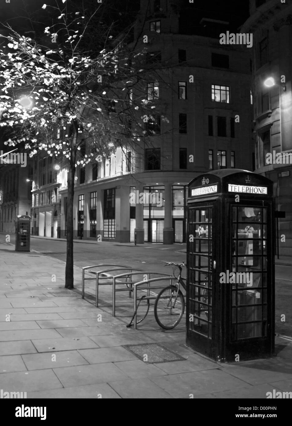Central London at night showing iconic telephone boxes, London, England, United Kingdom - Stock Image