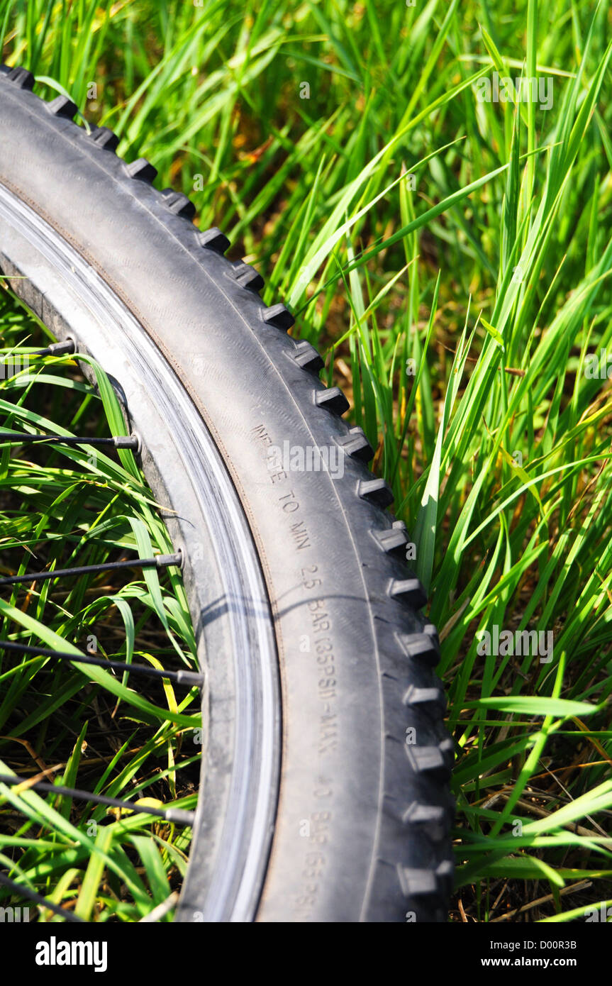 mountain bike offroad tire in green grass showing sport in nature concept - Stock Image