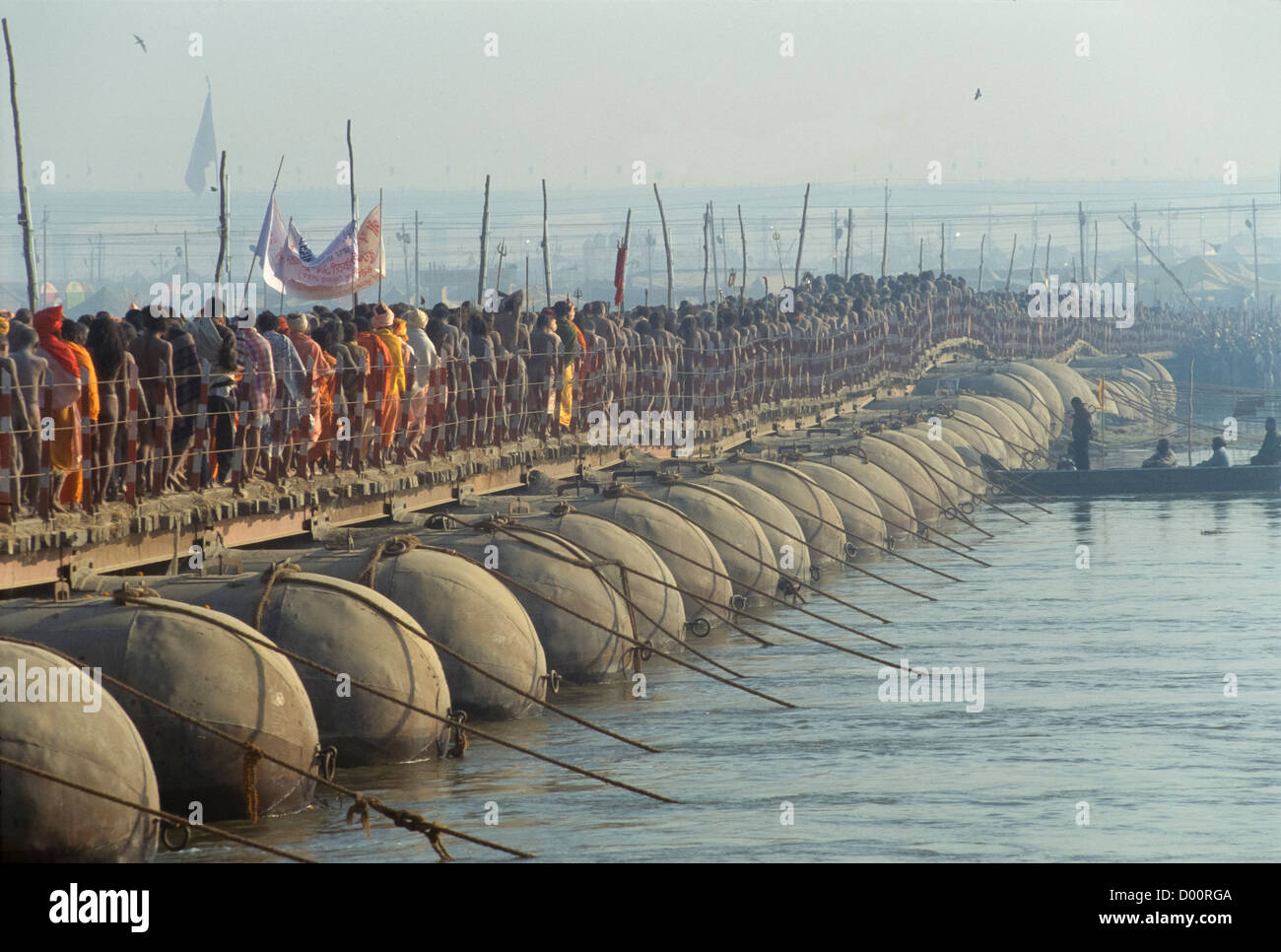 Naga sadhus from the Juna Akhara in procession across a pontoon bridge over the River Ganges, on the Basant Panchmi - Stock Image