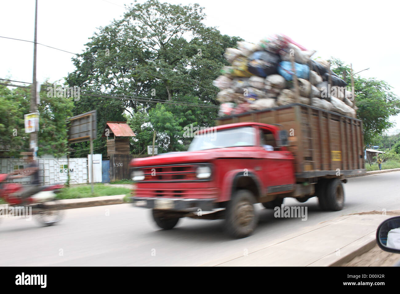 red truck transporting goods in developing country - Stock Image