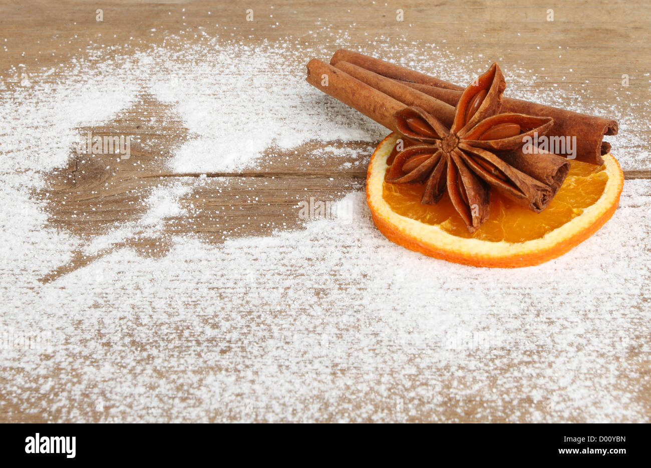 Christmas theme, dried orange, cinnamon and star anise on a wooden board with a shadow of holly in dusted icing - Stock Image