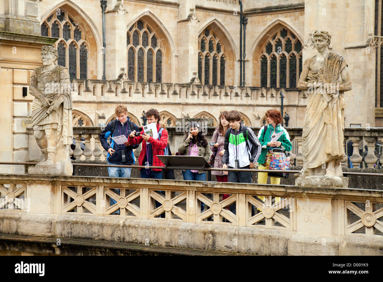 Teenage tourists at the abbey and Roman Baths in Bath Spa, Somerset, UNESCO World Heritage site, UK - Stock Image