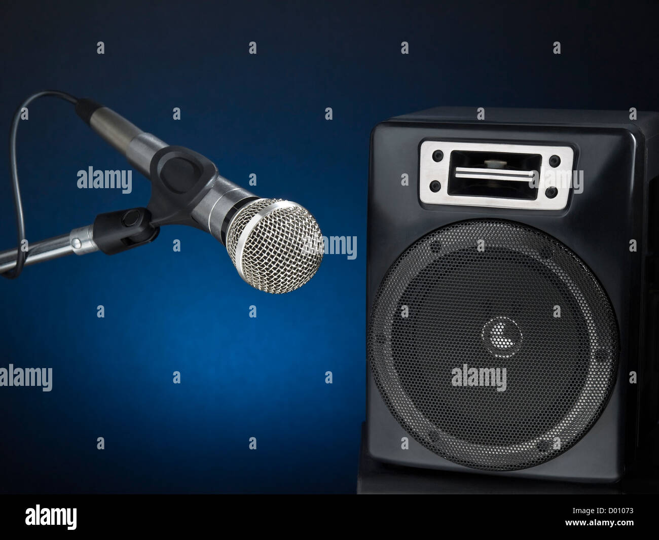 Professional microphone and speaker over a diffuse blue background. - Stock Image
