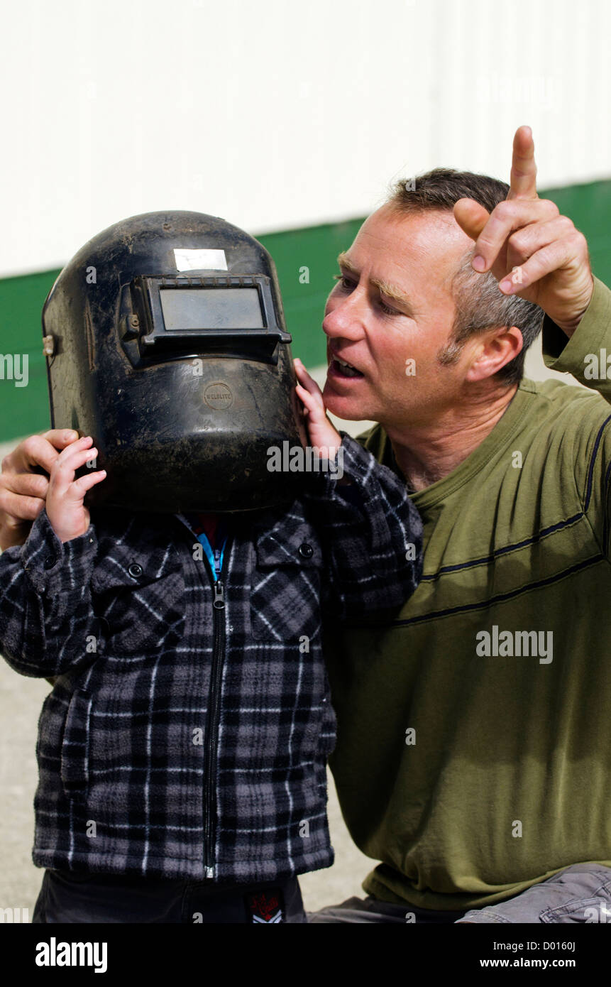 Father and son looks trough a welding mask at the partial solar eclipse passes over Northland New Zealand on November - Stock Image