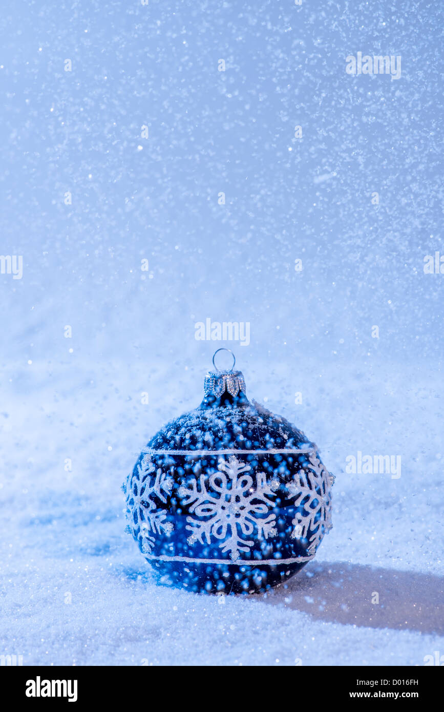 Blue Christmas Bauble in snow. Snowing. Copy space. - Stock Image