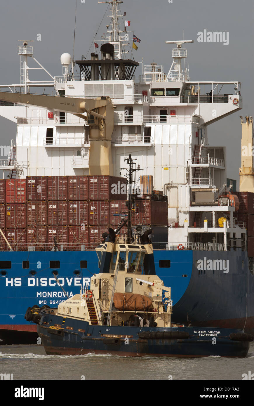 HS Discoverer container ship with tug - Stock Image