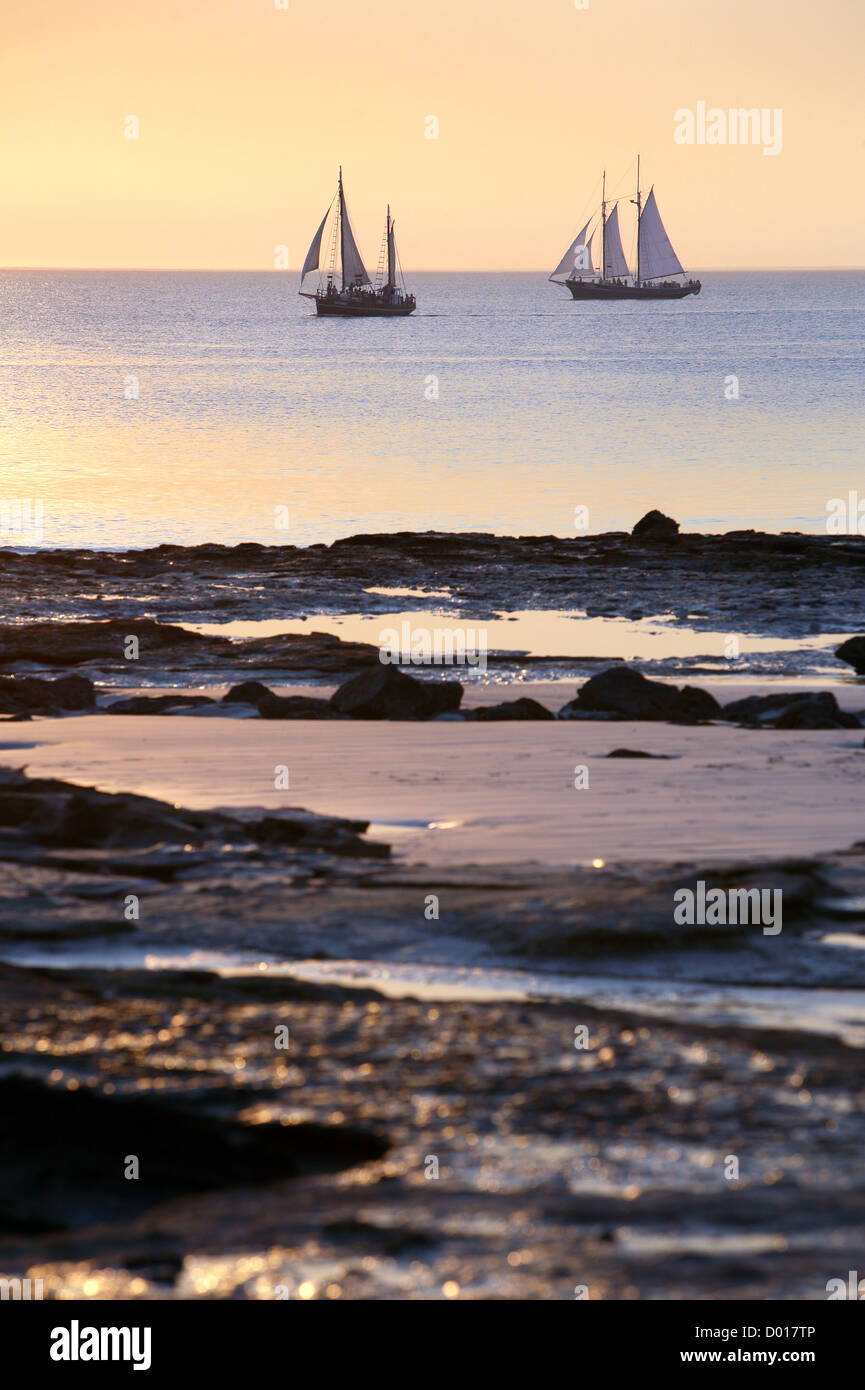 Pearl luggers cruising past Cable beach at sunset. Broome, Western Australia.  - Stock Image
