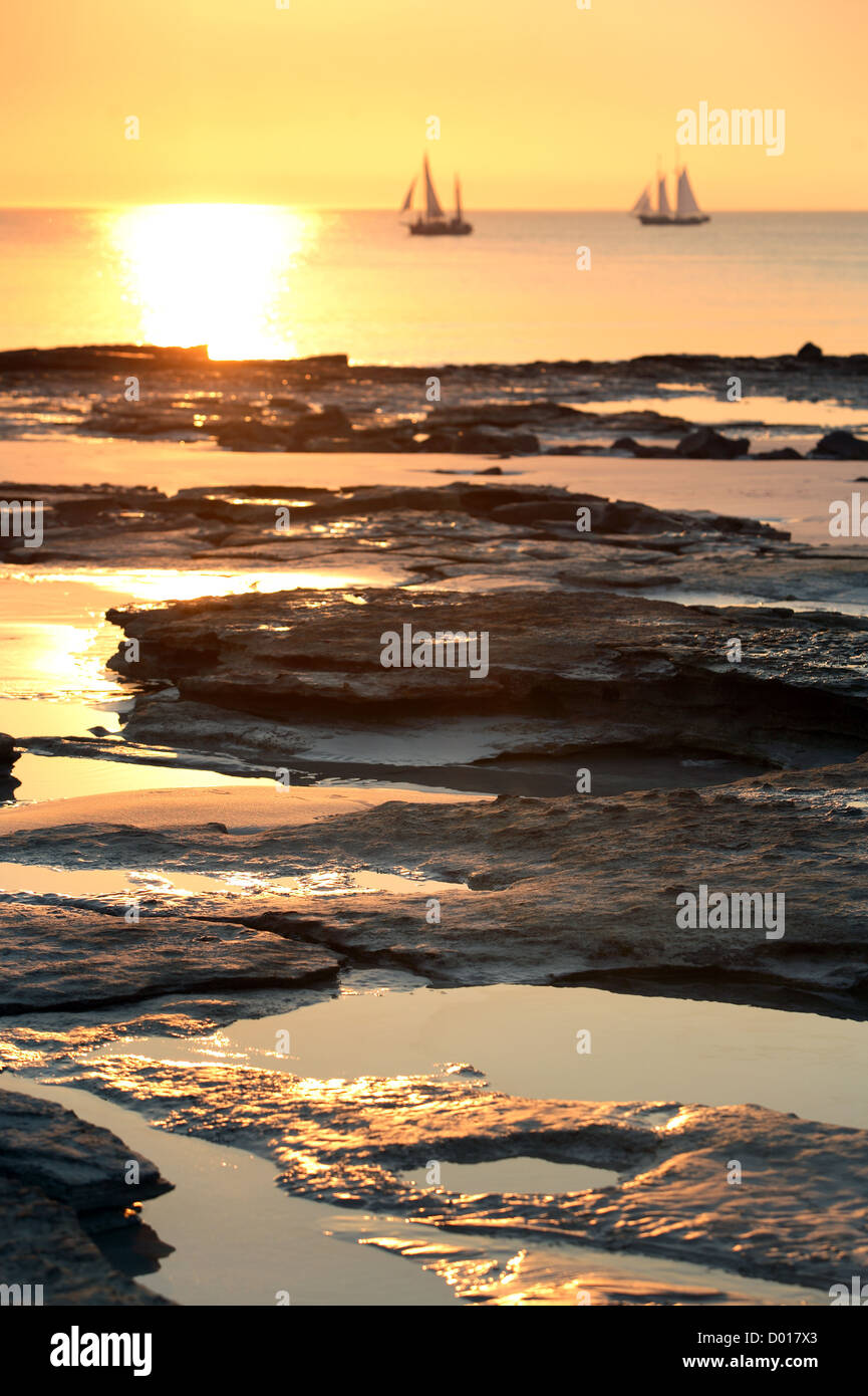 Pearl lugger cruising past Cable beach at sunset. Broome, Western Australia. - Stock Image