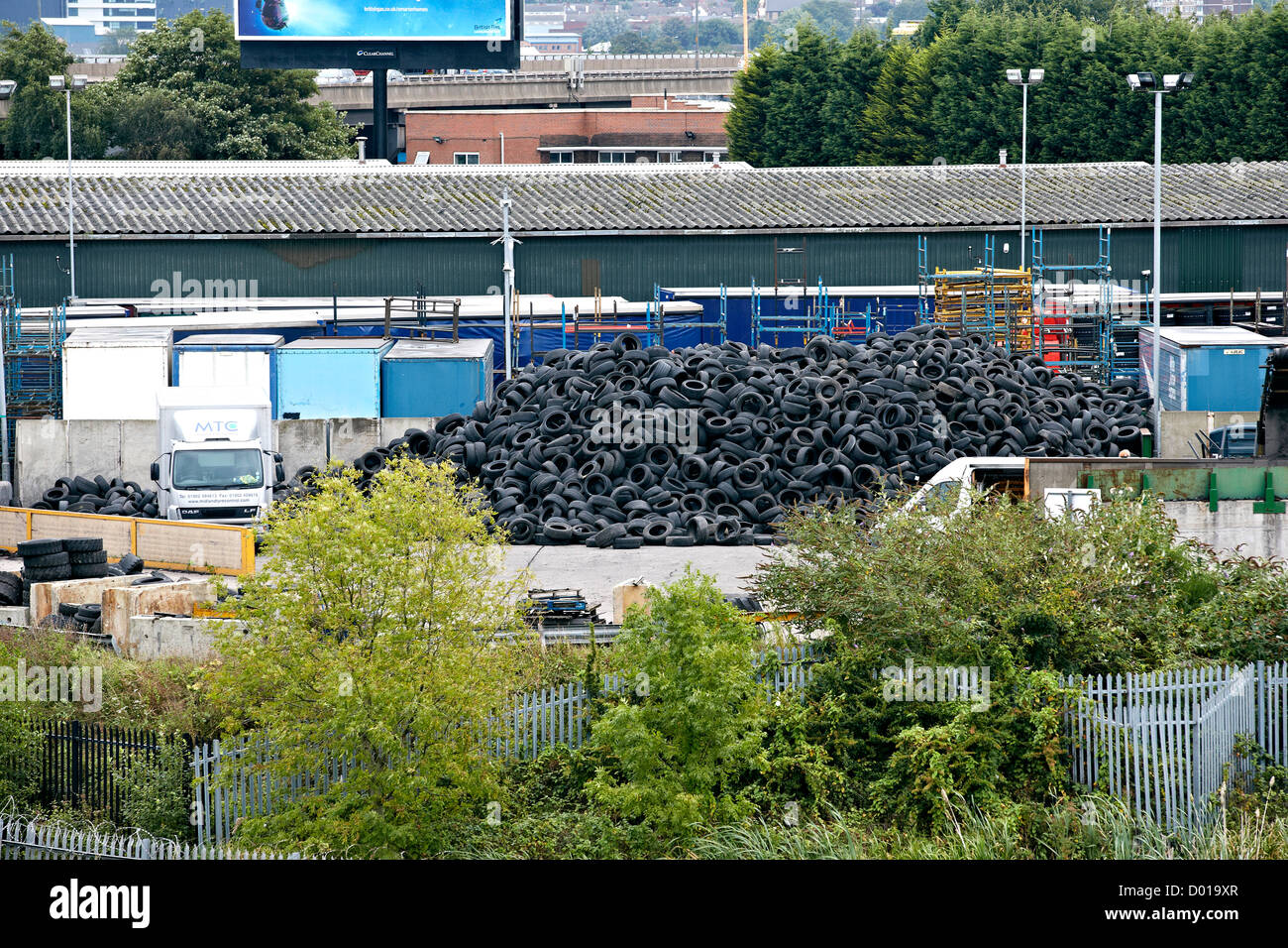 Old used car tyres tires piled on an industrial estate wait recycling into new products. - Stock Image