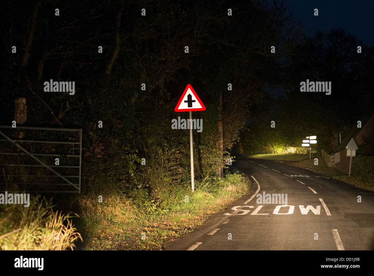 At a crossroads. Driving at night along country lanes negotiating crossroads in Worcestershire, UK. - Stock Image