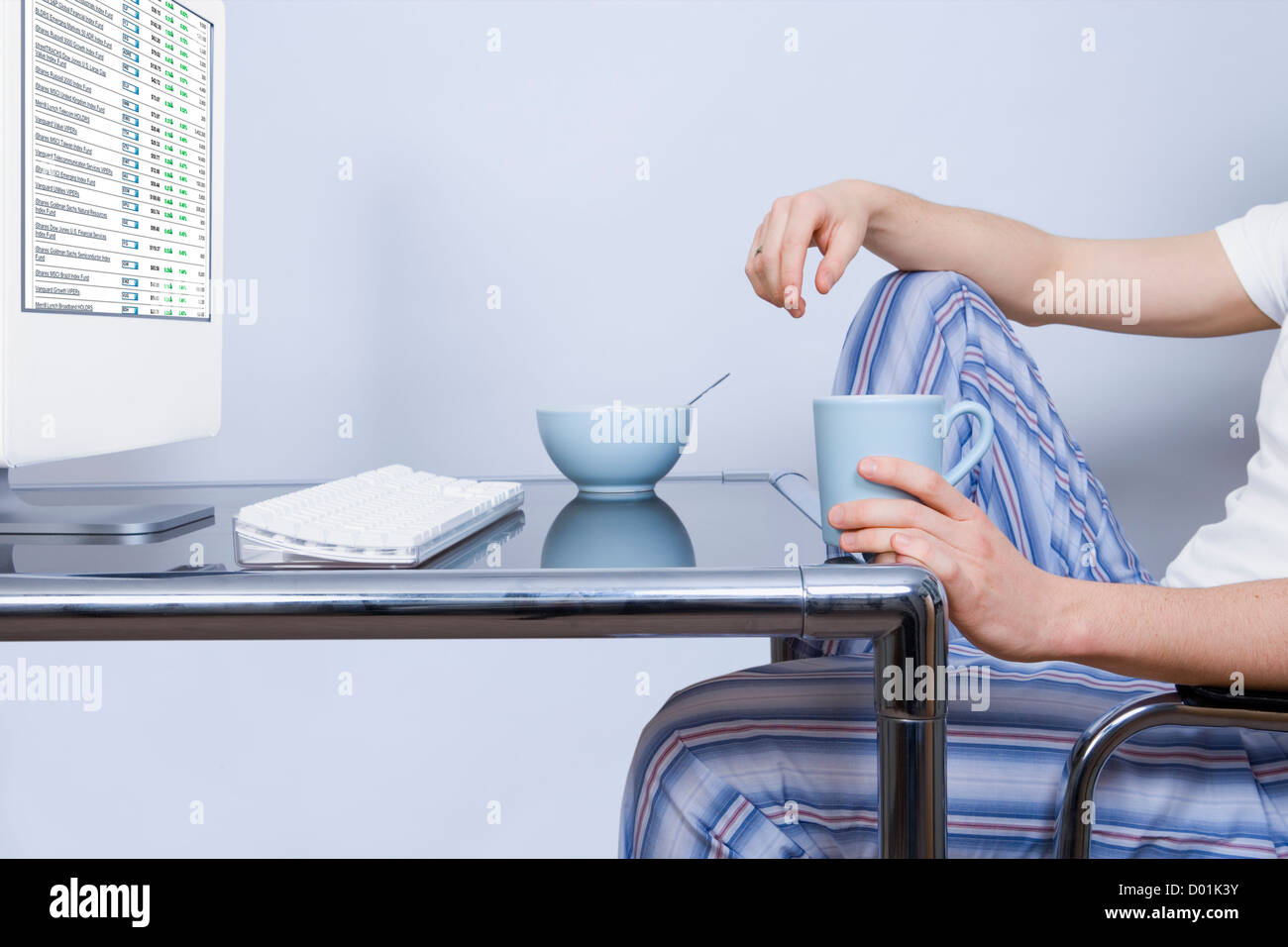 Young man in pyjamas sitting at computer desk holding cup - Stock Image
