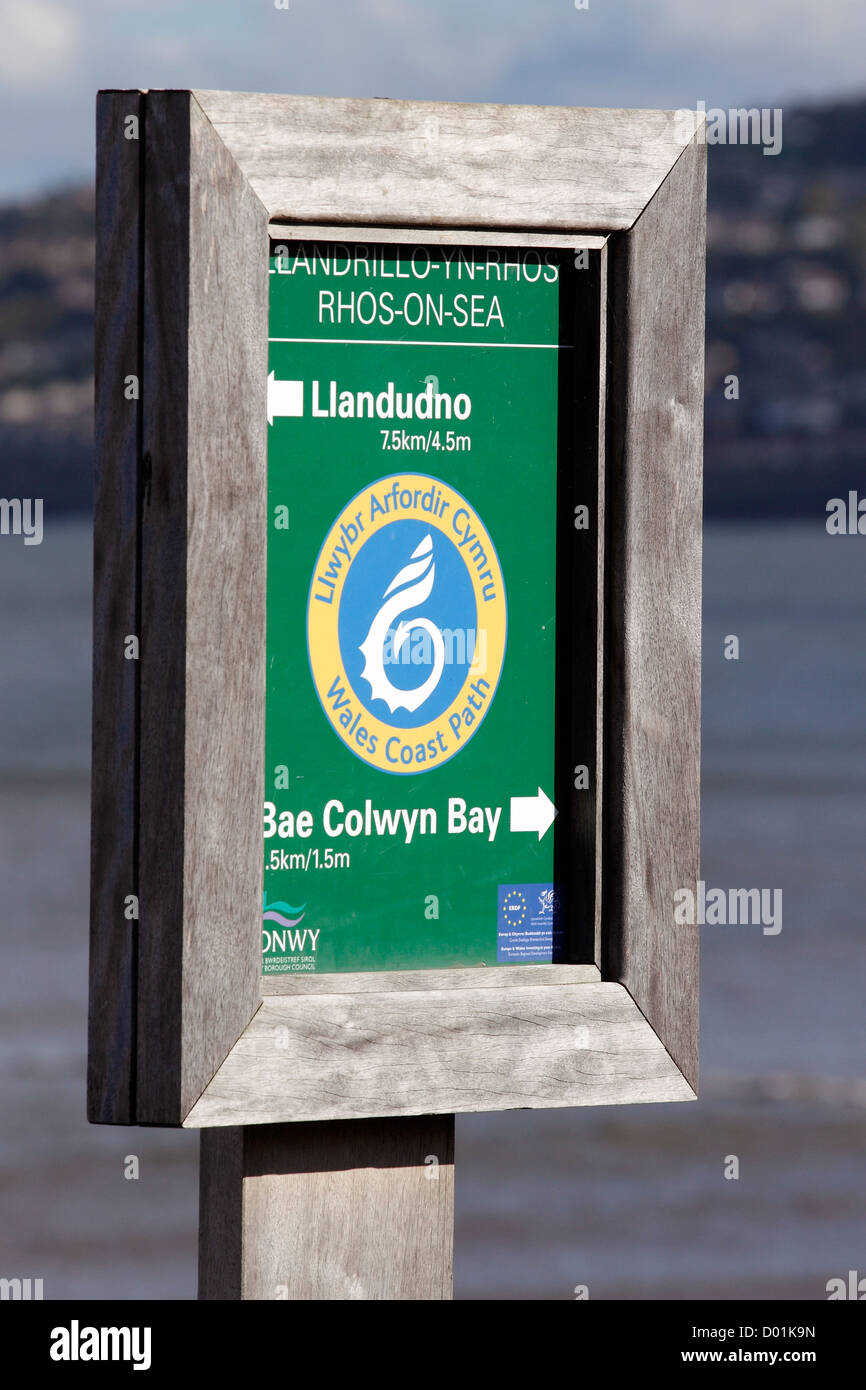 A Wales Coastal Path sign in Rhos on Sea, North Wales giving directions and distances to Llandudno and Colwyn Bay. - Stock Image