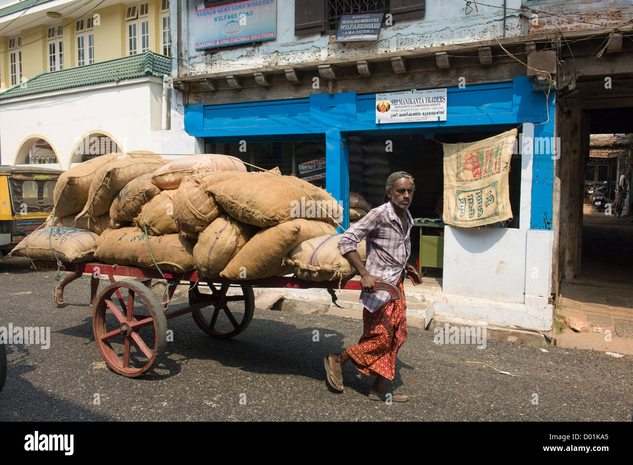 Man pulling a handcart loaded with jute sacks, Bazaar Road, Fort Cochin, Kochi (Cochin), Kerala, India - Stock Image