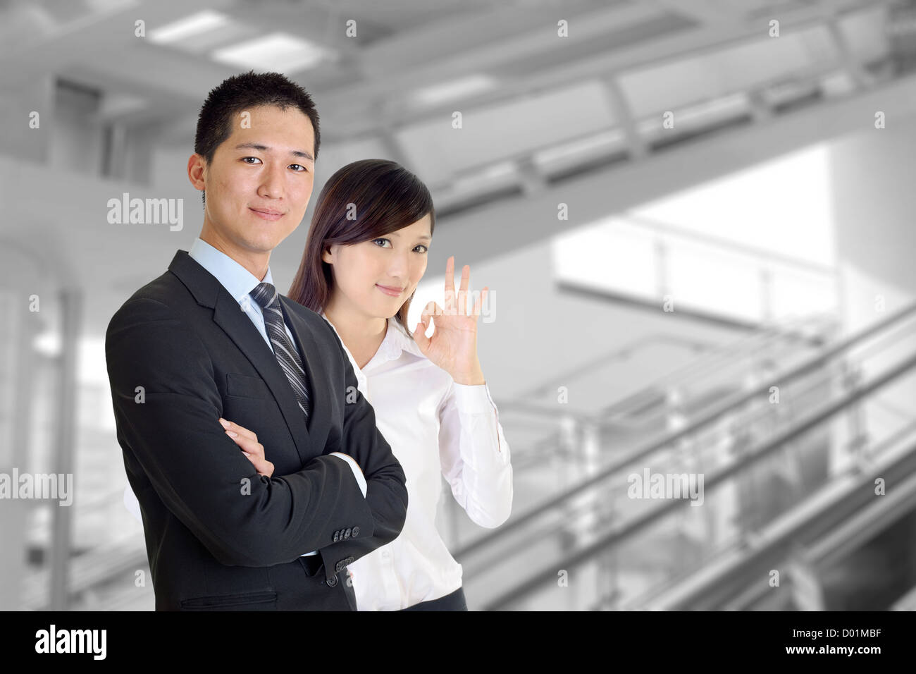 Business team, smiling businessman and friendly businesswoman in modern building. - Stock Image