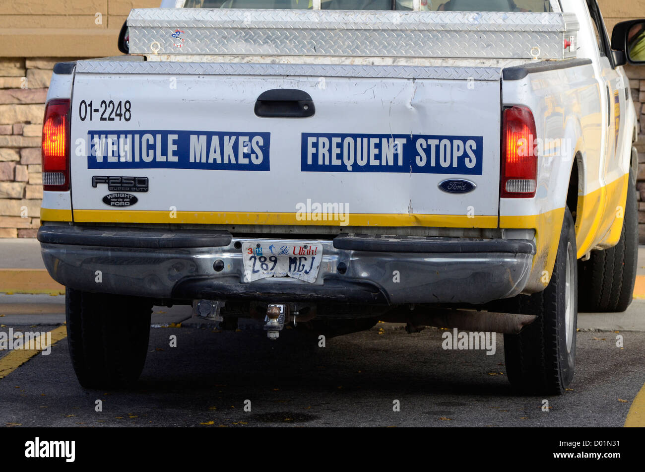 Dented truck with 'Vehicle Makes Frequent Stops' sign. - Stock Image