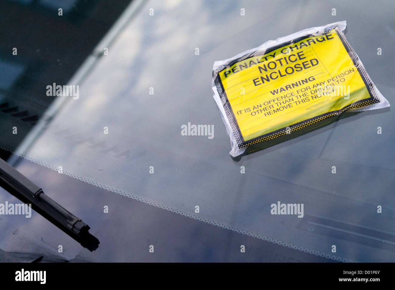 Penalty charge notice parking ticket on car windscreen. - Stock Image