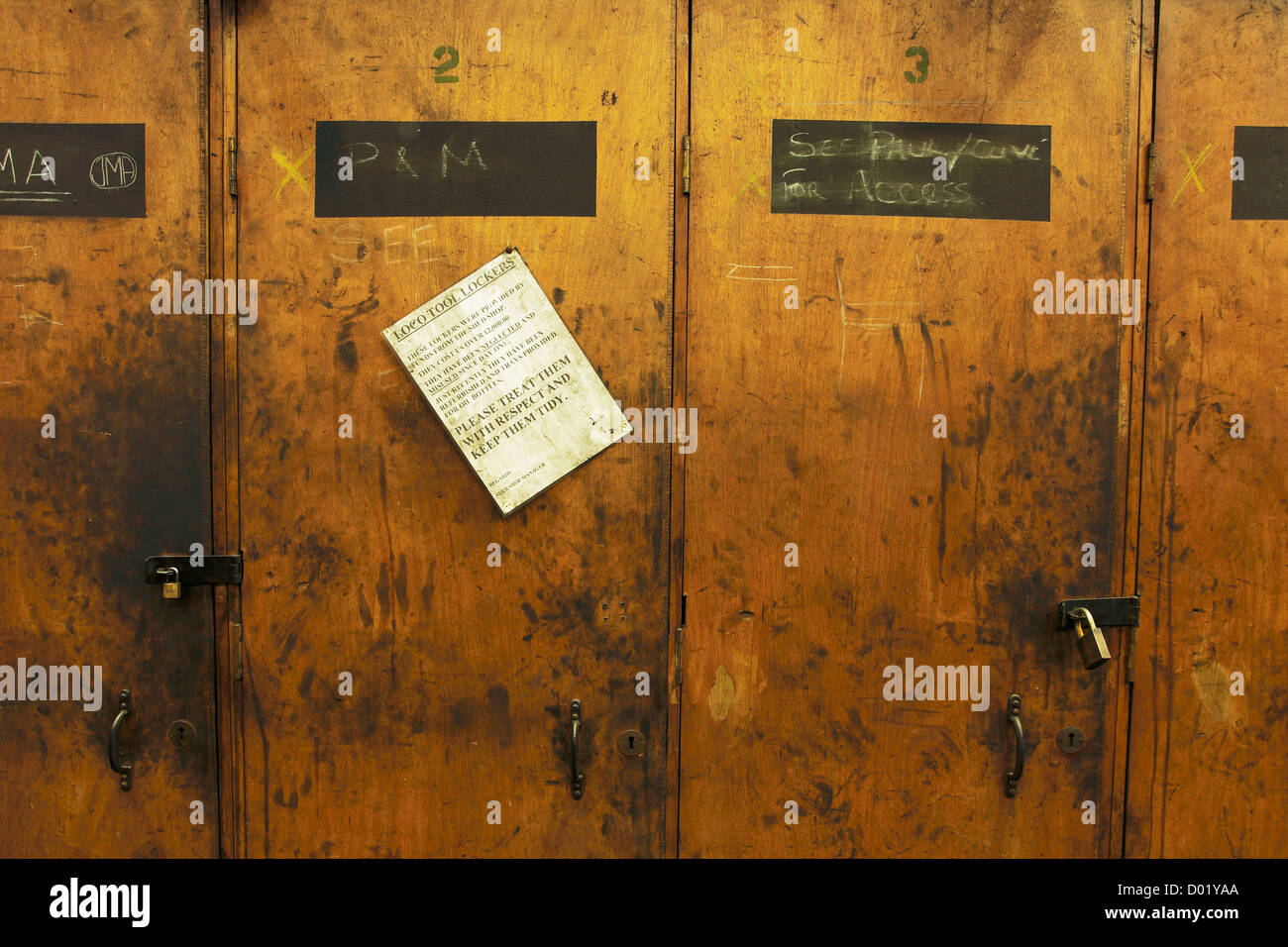 Some old worn out and abused wooden lockers with an amusing sign asking for them 'to be treated with respect' - Stock Image