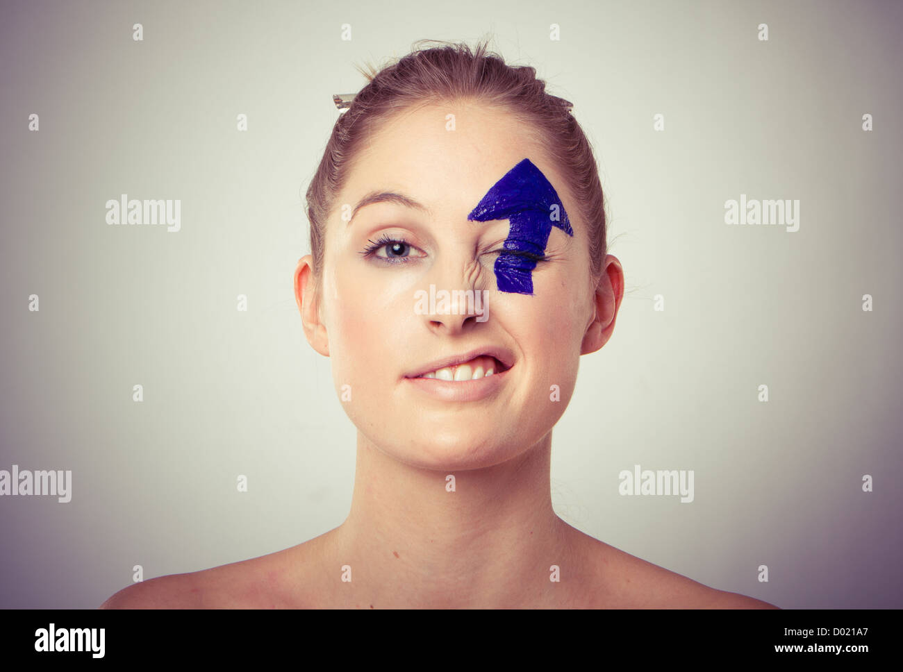 Portrait of smiling young blond haired woman with upward pointing arrow painted over eye, white studio background. - Stock Image