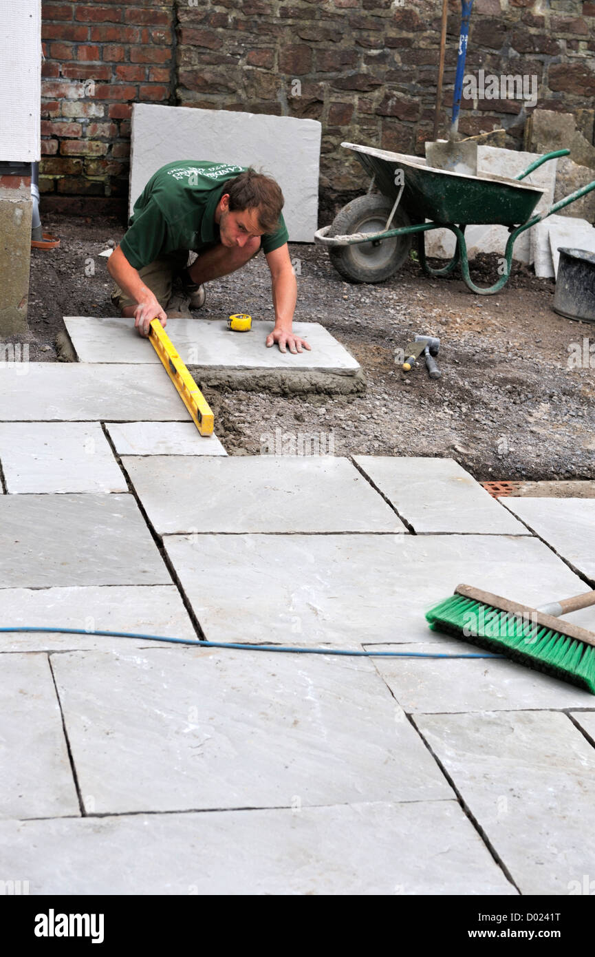 Using a level while installing natural stone paving slabs Stock Photo