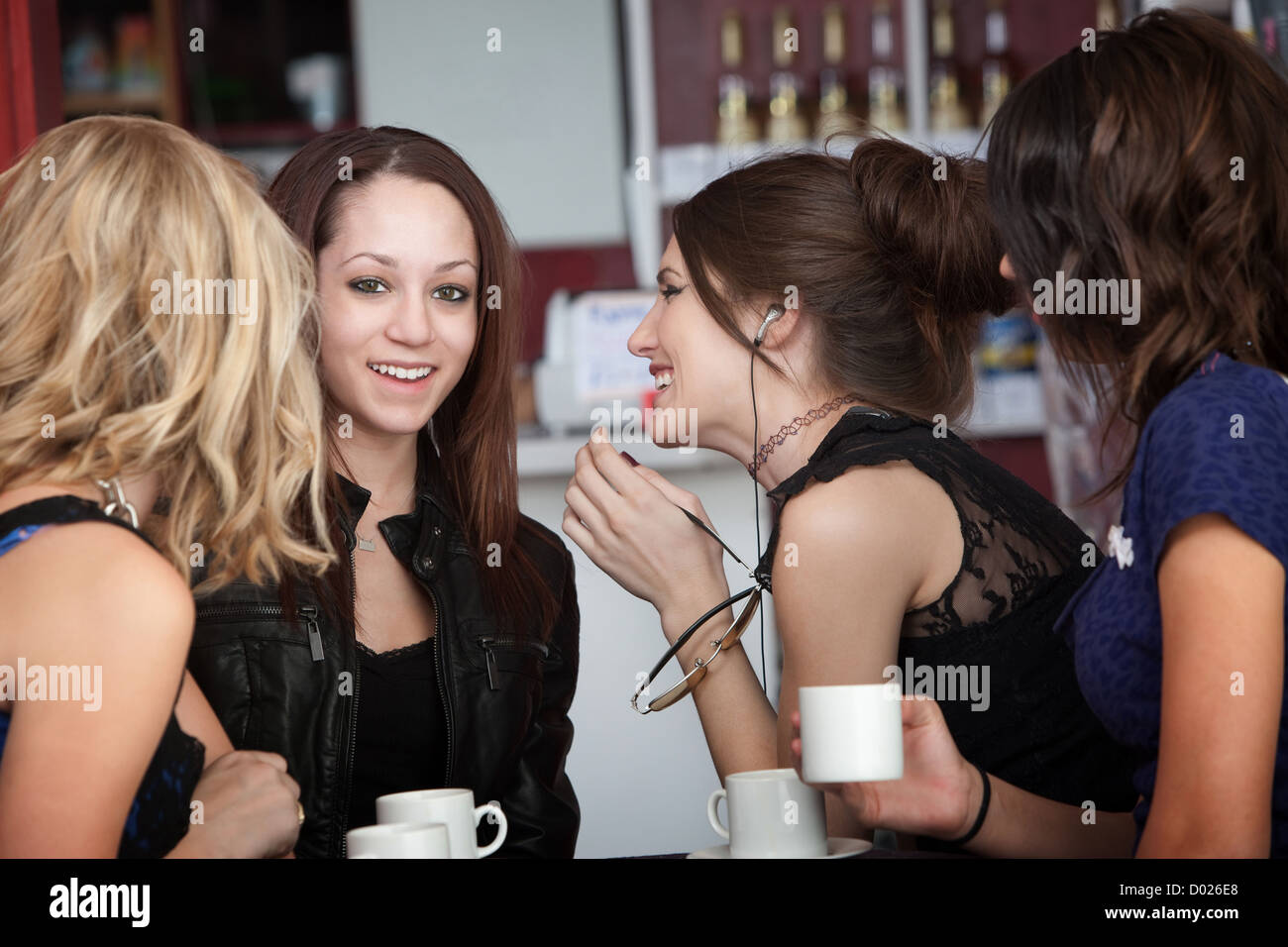 Four young women sharing secrets at a cafe - Stock Image