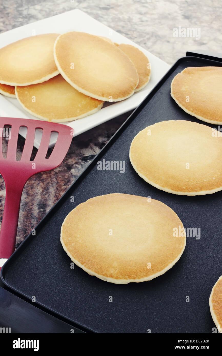 Preparing fresh pancakes on a non-stick griddle. - Stock Image