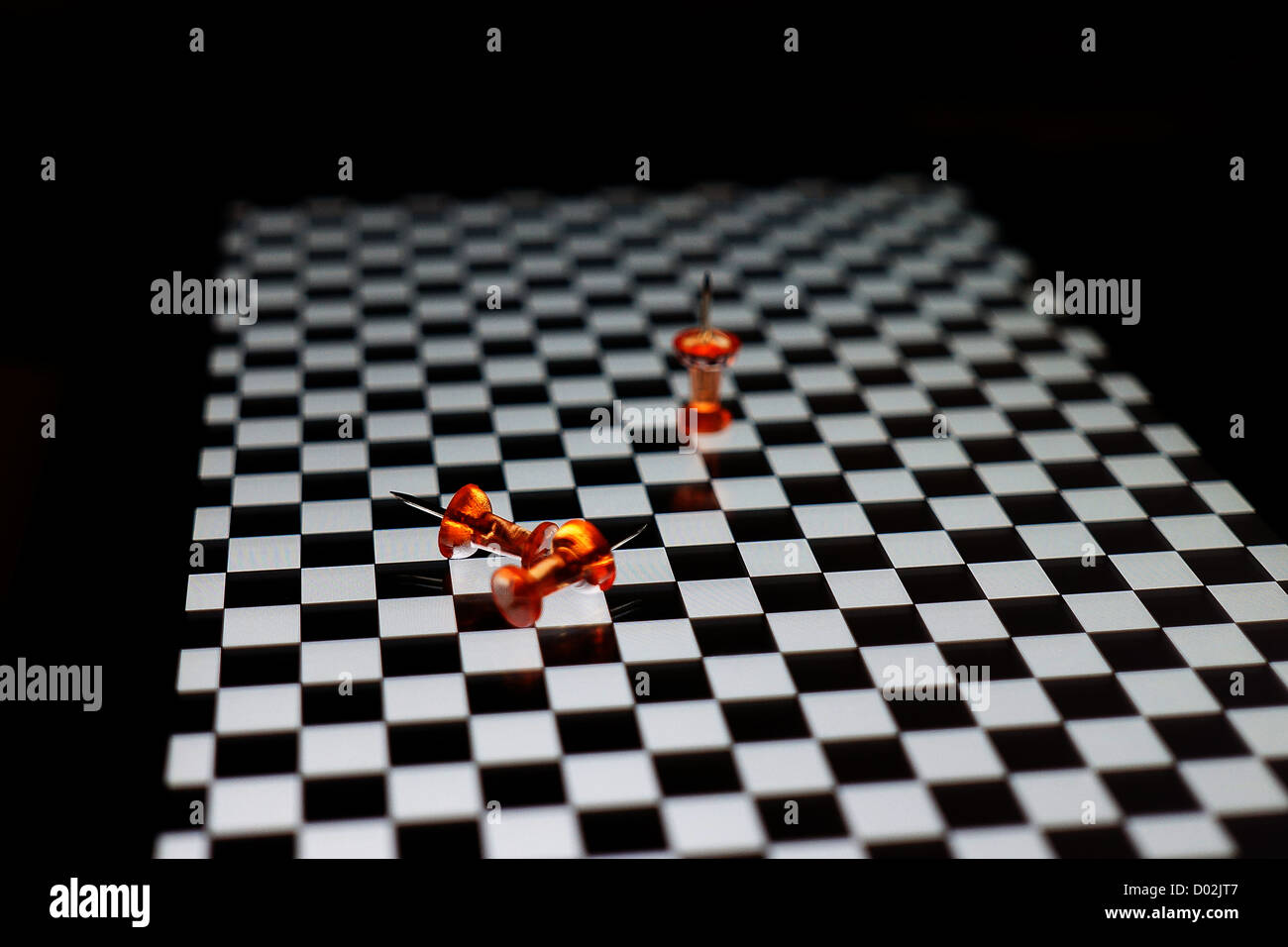 Orange drawing pins on chequered surface - Stock Image