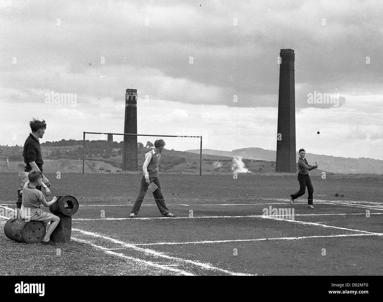 Boys playing tennis on home made court in Blowers Green Dudley with chimney stacks of Stourbridge Glazed Brick Company - Stock Image