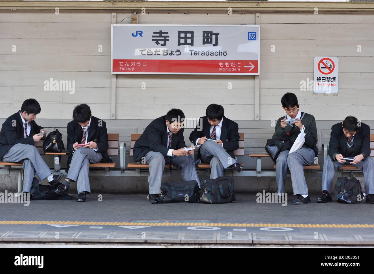 School kids in Osaka, Japan, lost in their smartphones. - Stock Image