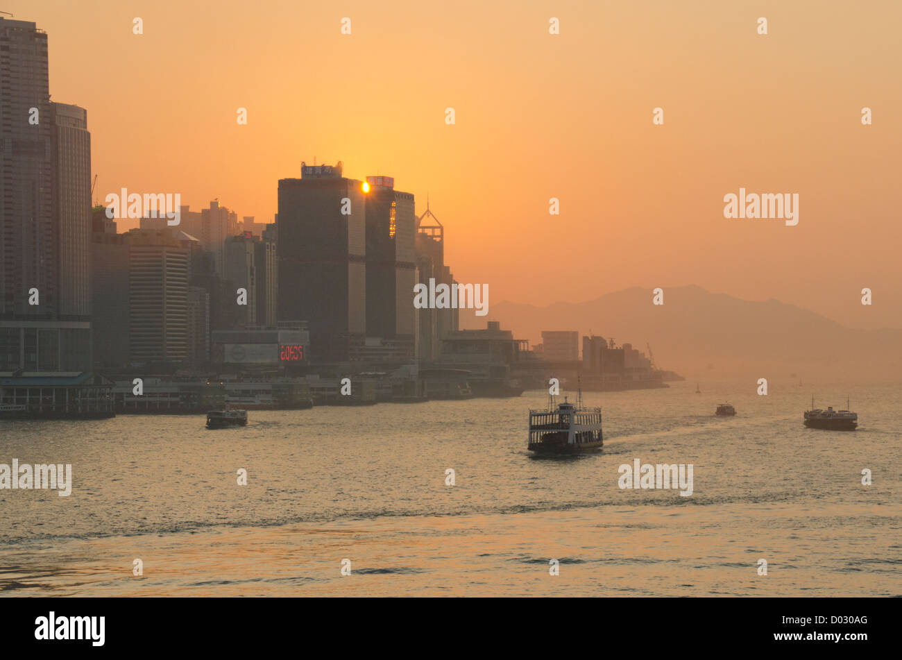 China, Hong Kong. Sunset view of Honk Kong Island from Victoria Harbor & Kowloon. - Stock Image