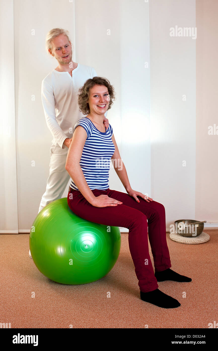 adult practicing poses on exercise ball with professional - Stock Image
