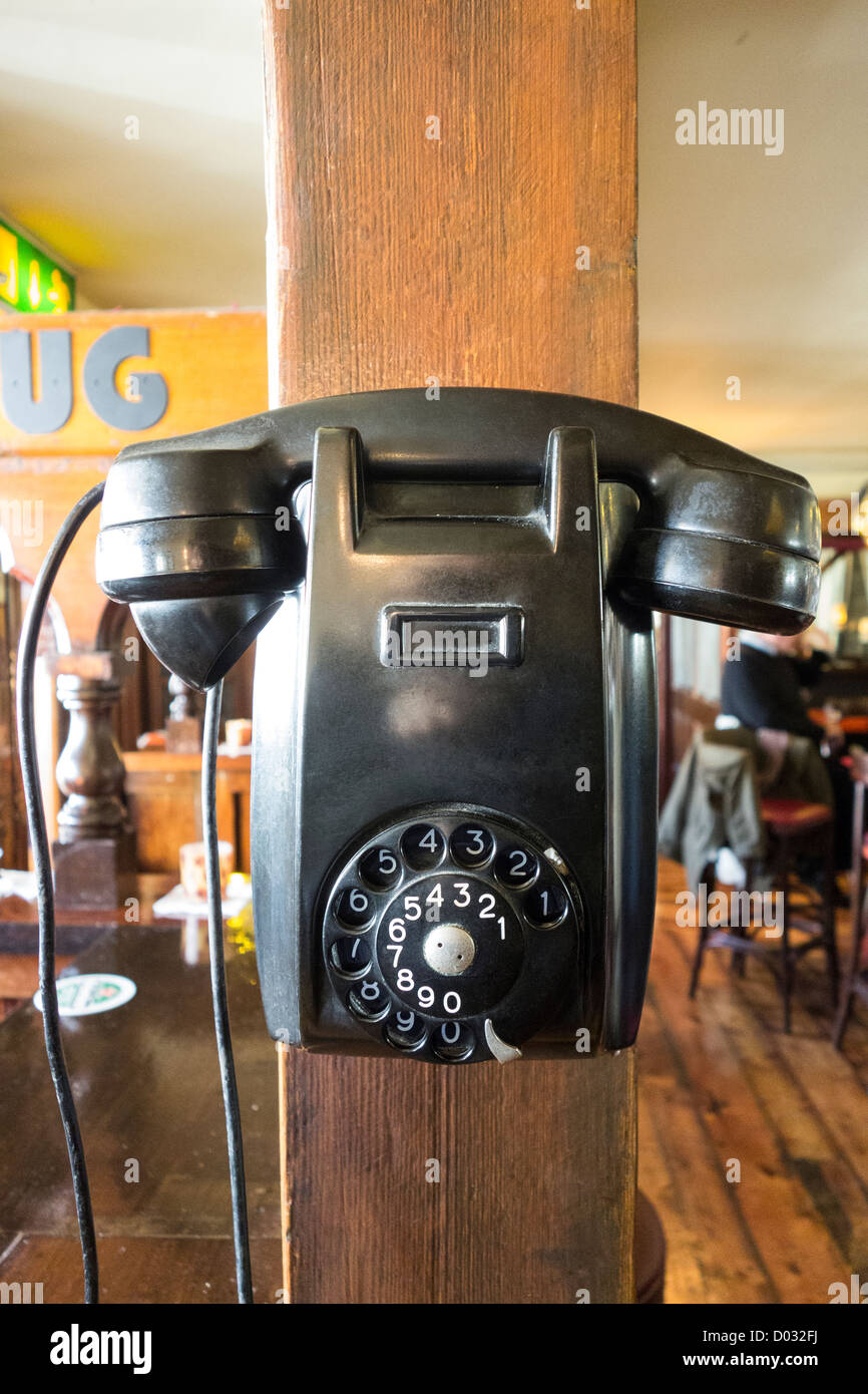 A very old rotary telephone mounted as a decoration on the wall of an Irish pub - Stock Image