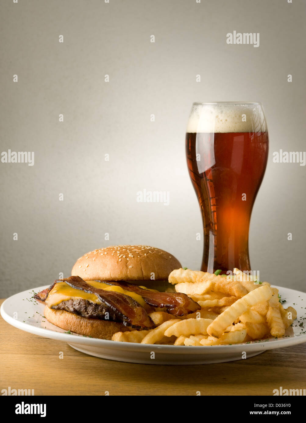 Crinkle cut fries and a bacon cheeseburger on a sesame seed bun is perfectly paired with a nice cold beer. Plenty - Stock Image