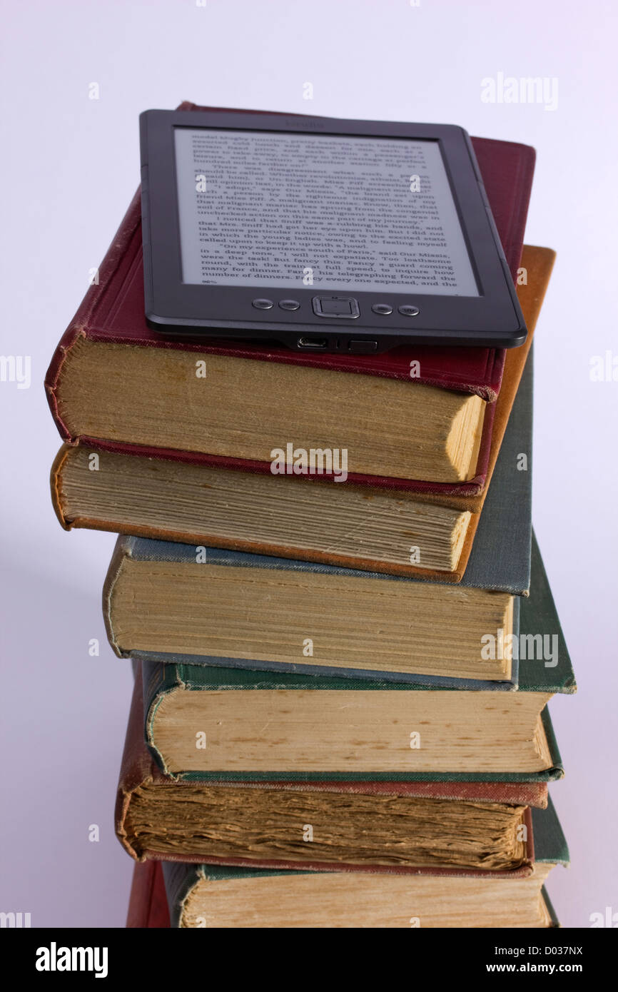 Pile of old books with Kindle eBook reader - Stock Image