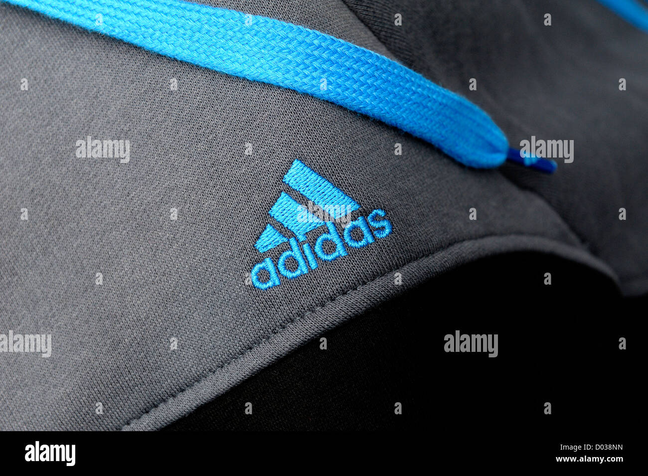 Adidas logo in blue stitched onto a tracksuit top - Stock Image