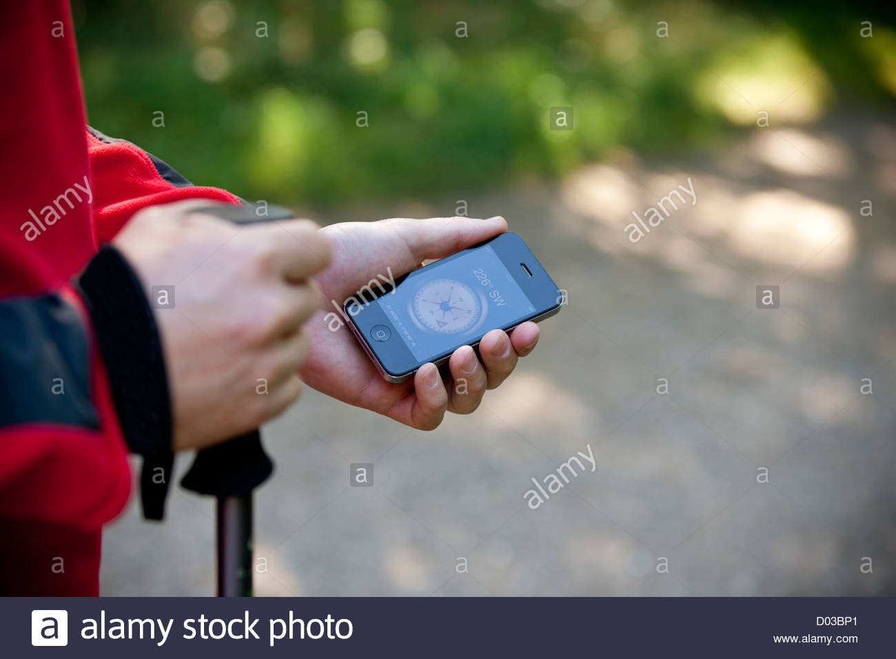 A man holding a smartphone with a compass application, close up - Stock Image