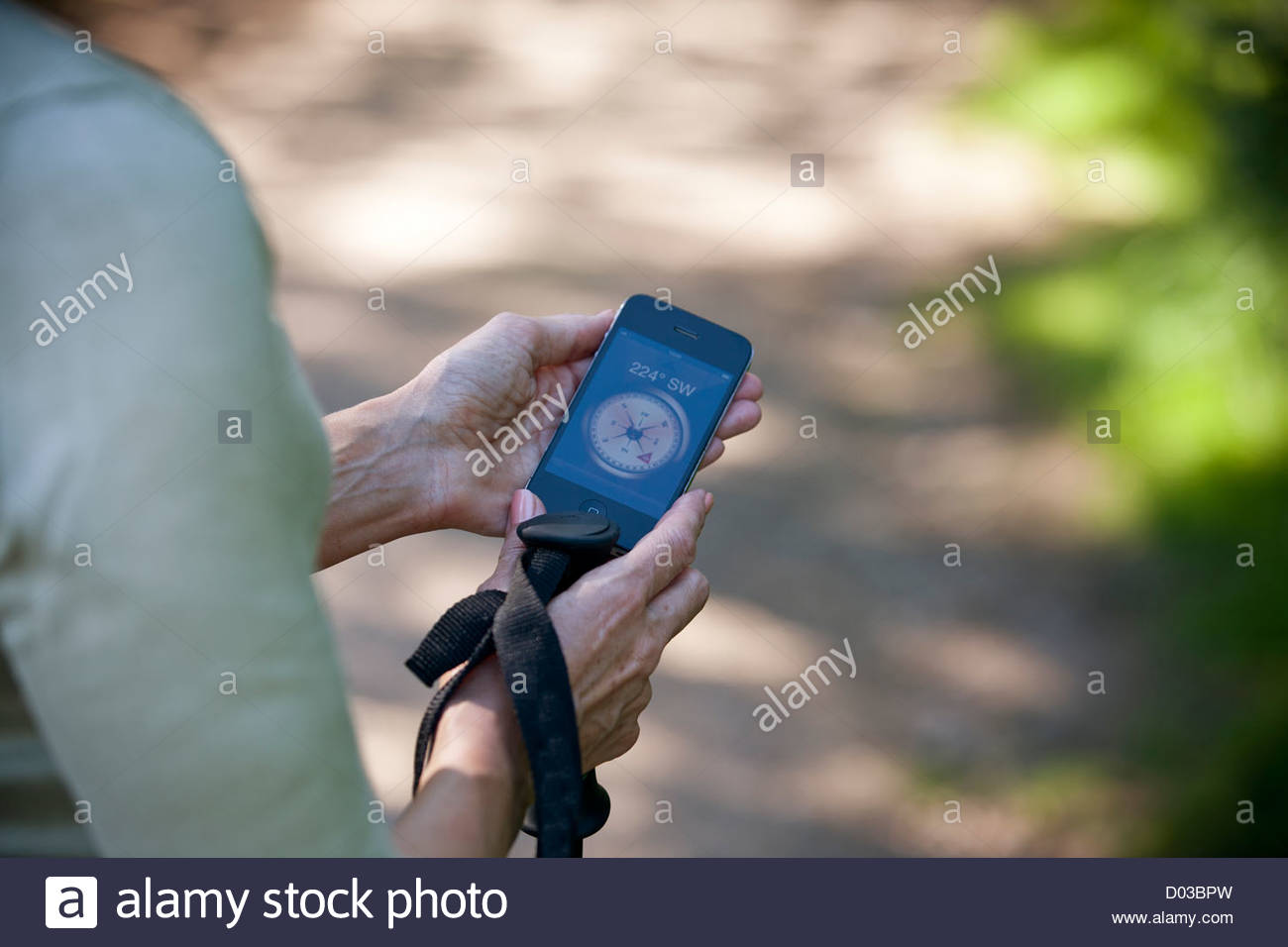 A woman holding a smartphone with a compass application, close uo - Stock Image