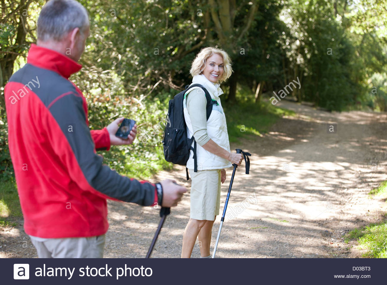 A mature couple walking along a country path, navigating with a smartphone - Stock Image