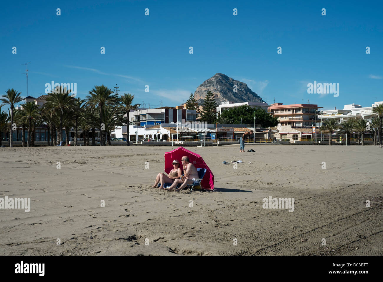 Sunbathers on the beach at Javea, Spain using a parasol to protect from the wind. - Stock Image