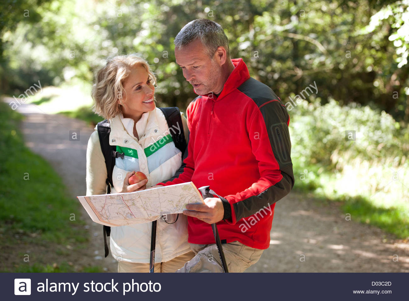 A mature couple walking in the countryside, holding a map Stock Photo