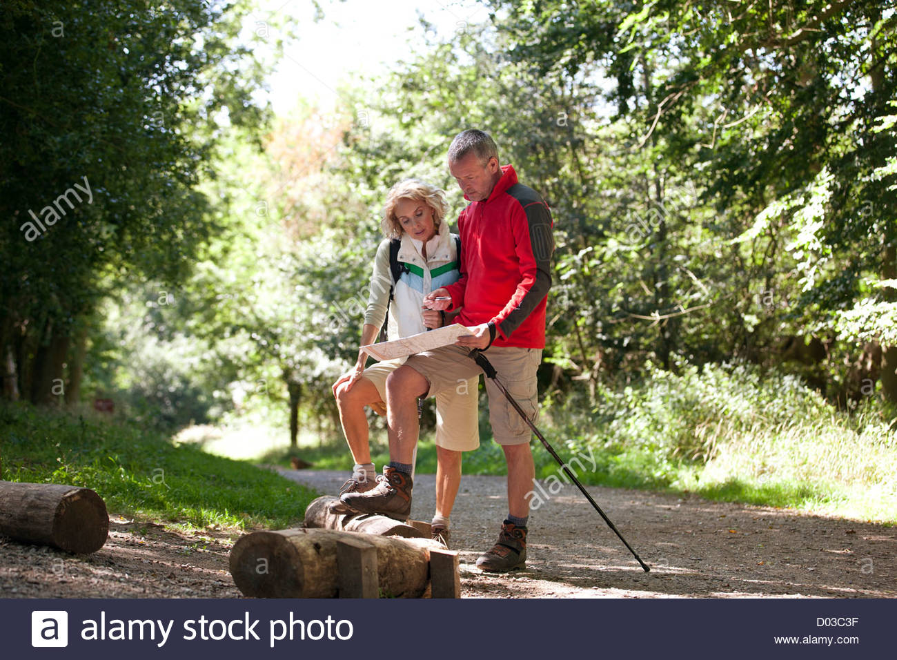 A mature couple standing on a country path, looking at a map - Stock Image