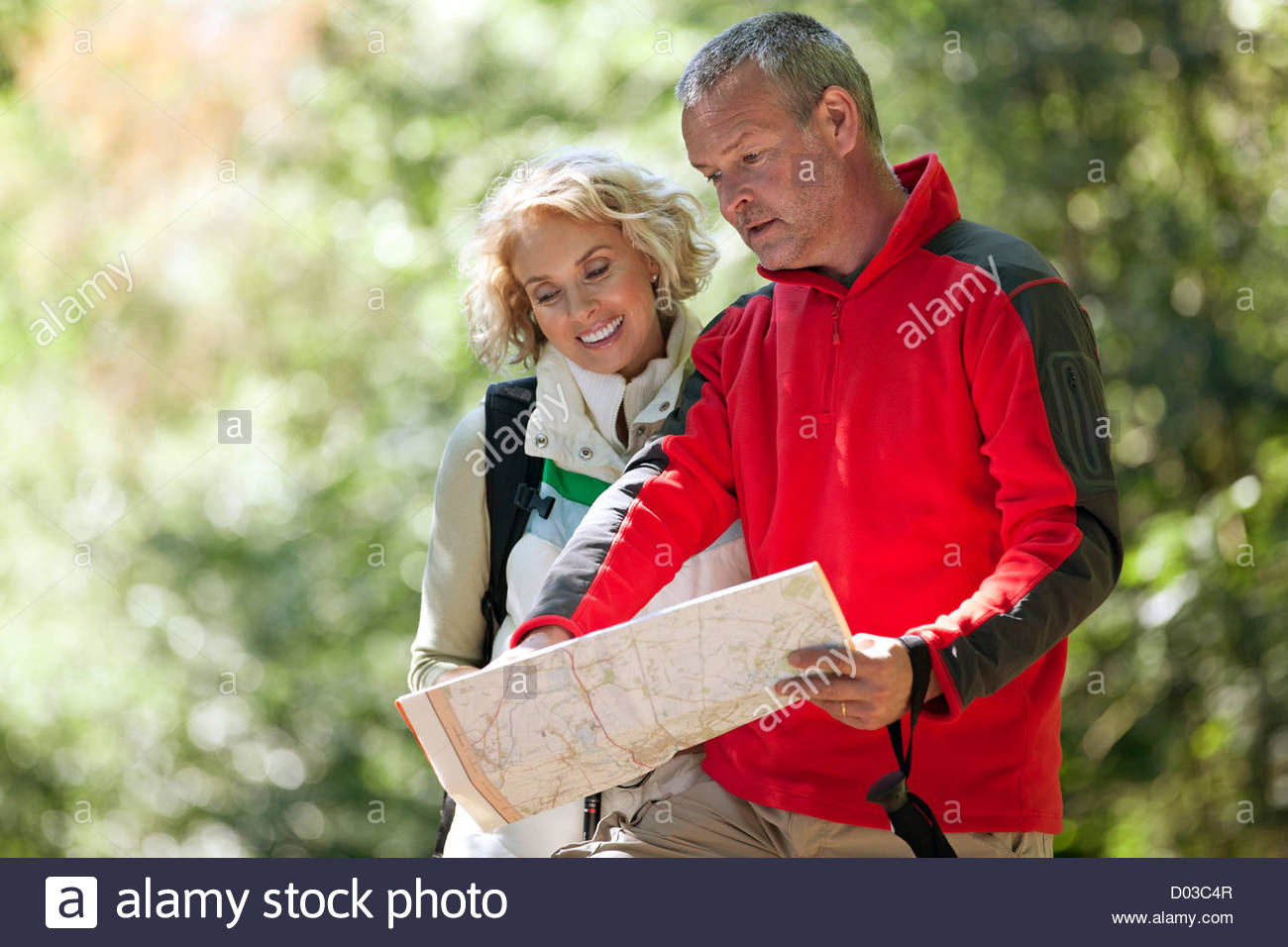 A couple walking in the countryside, looking at a map - Stock Image