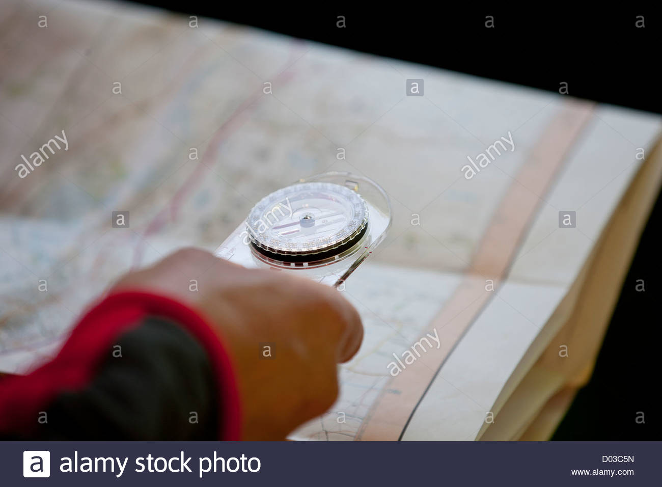 A man holding a map and compass, close up - Stock Image