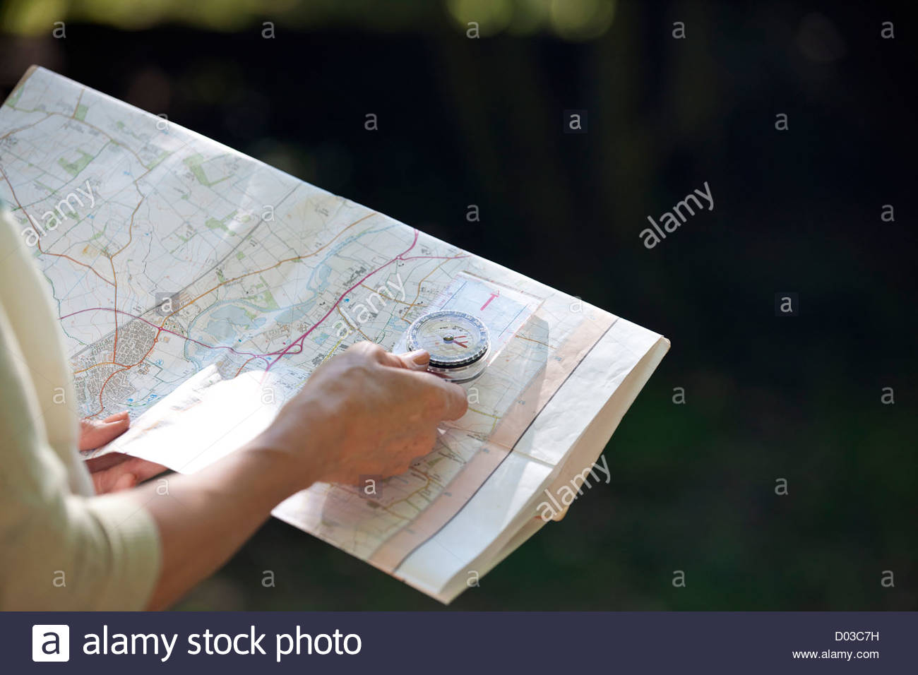 A woman holding a map and compass, close up - Stock Image