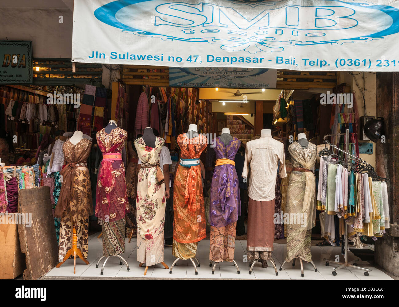 Shops dealing in traditional textiles in Sulawesi Street, Denpasar, Southern Bali, Indonesia. - Stock Image