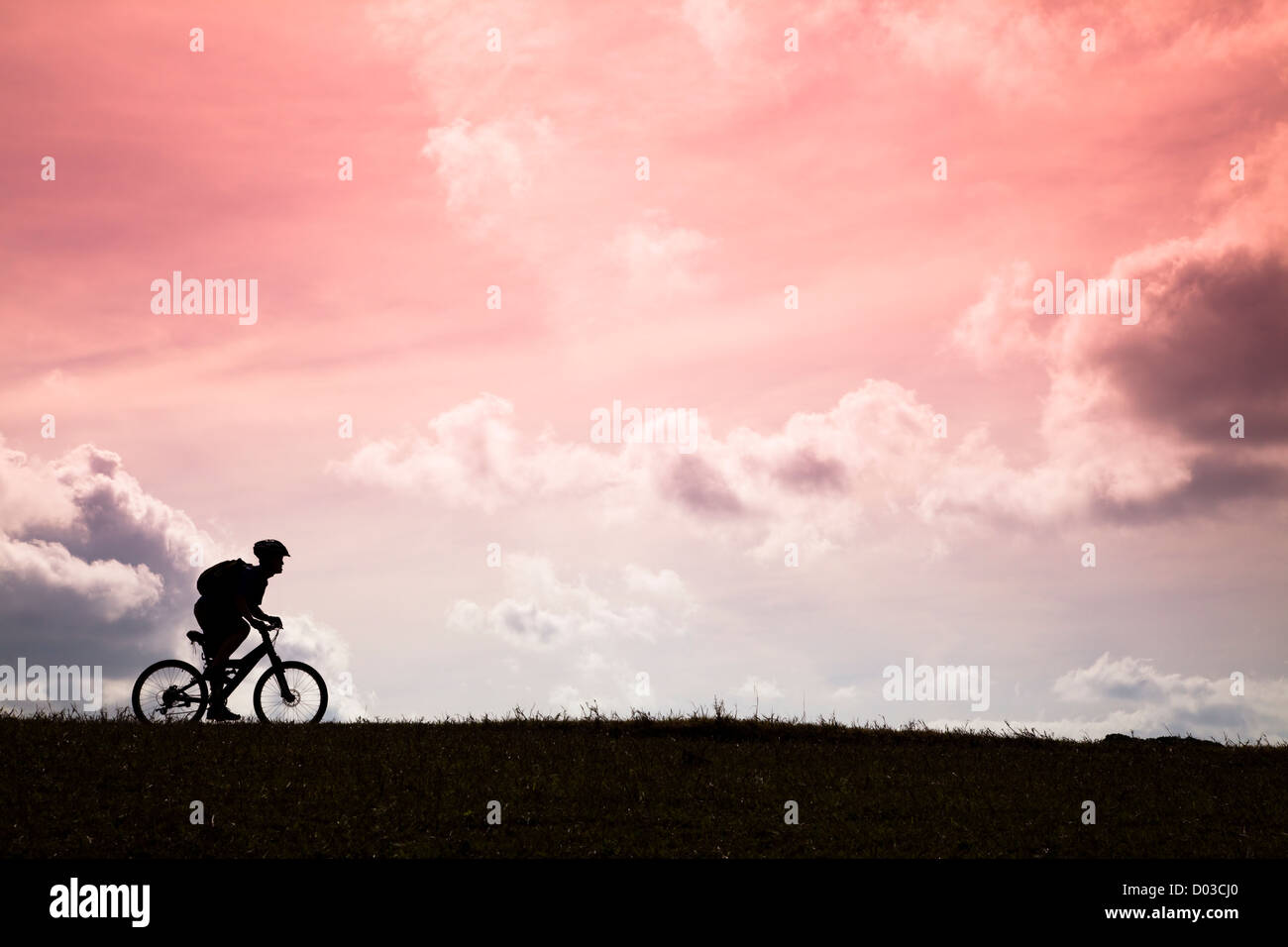 The Silhouette of mountain bike rider and sunset - Stock Image