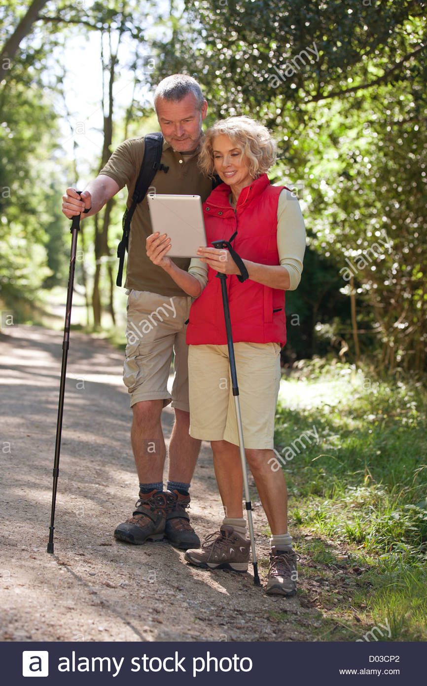 A mature couple out walking on a country path, navigating with an ipad - Stock Image