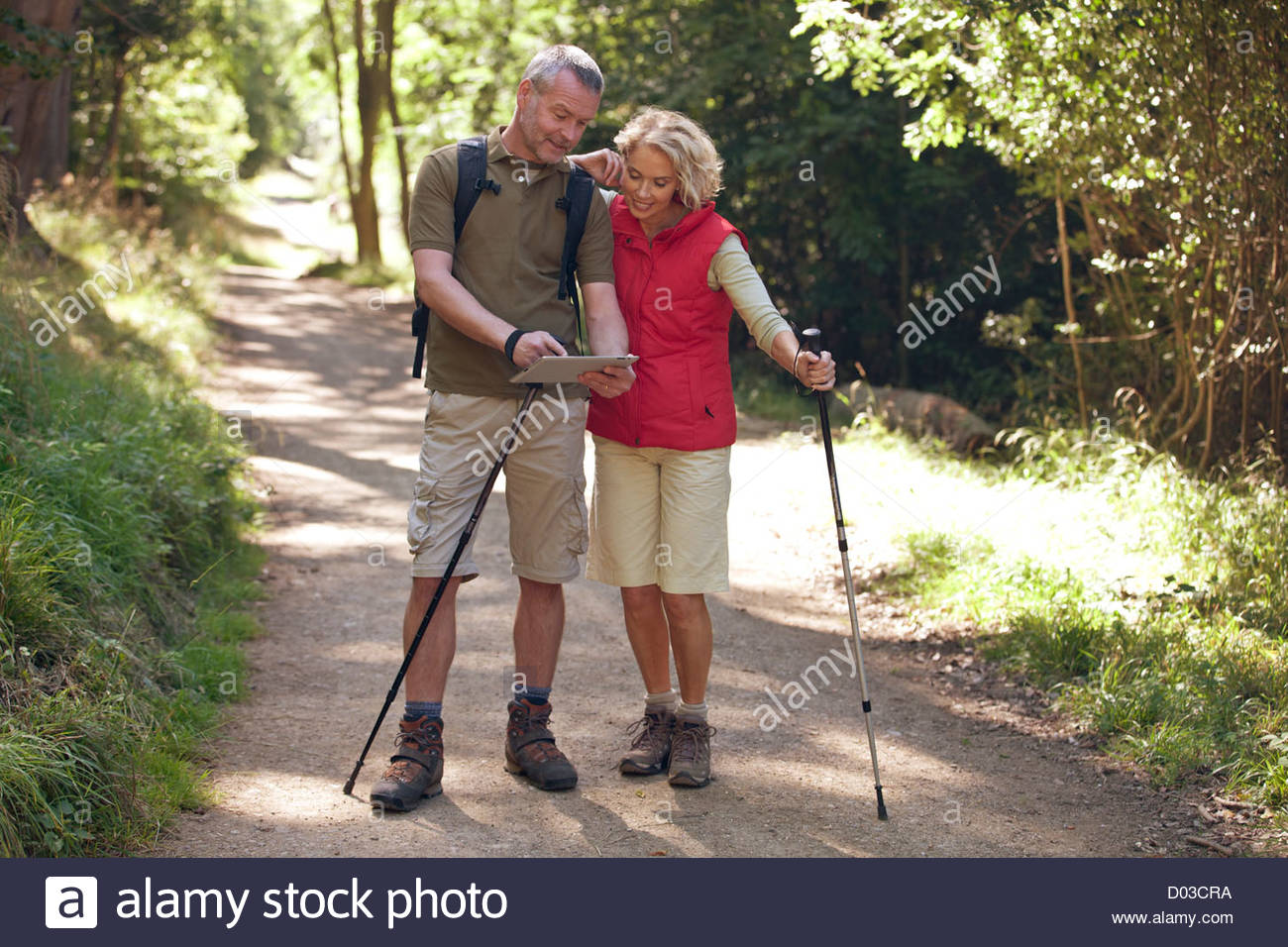 A mature couple out walking on a country path, navigating with a digital tablet - Stock Image